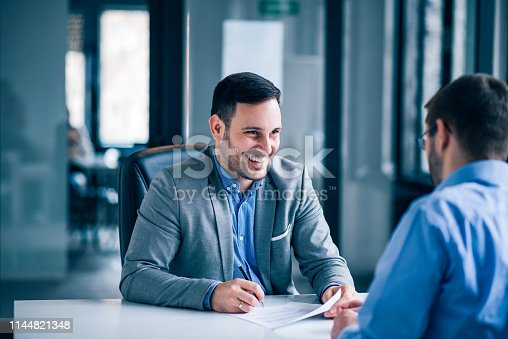 Handsome male client signing document on a meeting with real estate agent.
