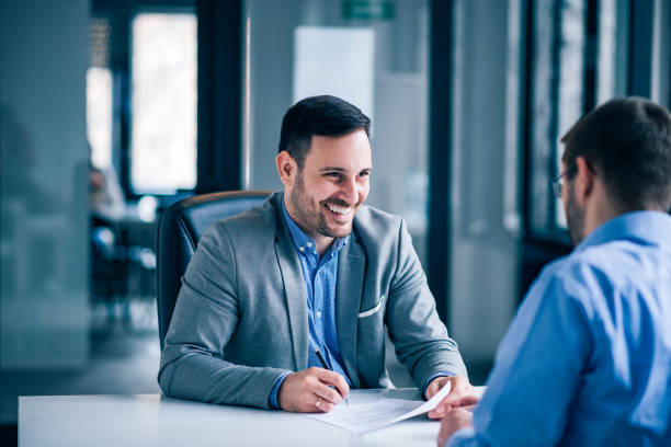 Handsome male client signing document on a meeting with real estate agent. Handsome male client signing document on a meeting with real estate agent. signing stock pictures, royalty-free photos & images