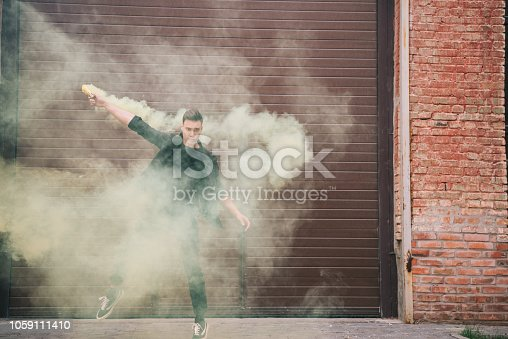 istock handsome male contemporary dancer in yellow smoke on urban city street 1059111410
