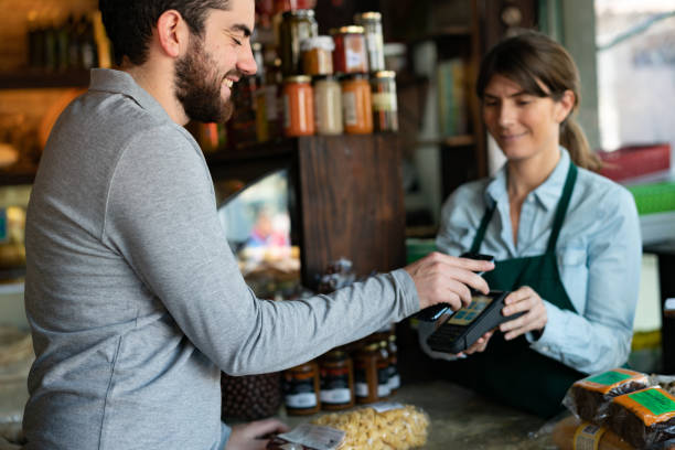 Handsome male customer at a delicatessen buying products making a contactless payment with smartphone Handsome male customer at a delicatessen buying products making a contactless payment with smartphone - Small business concepts homegrown produce stock pictures, royalty-free photos & images