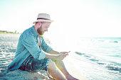 Handsome Male Enjoying Social Media At The Beach