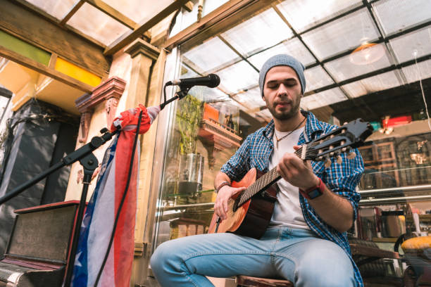 Guapo masculino guitarrista disfrutando de música en guitarra - foto de stock