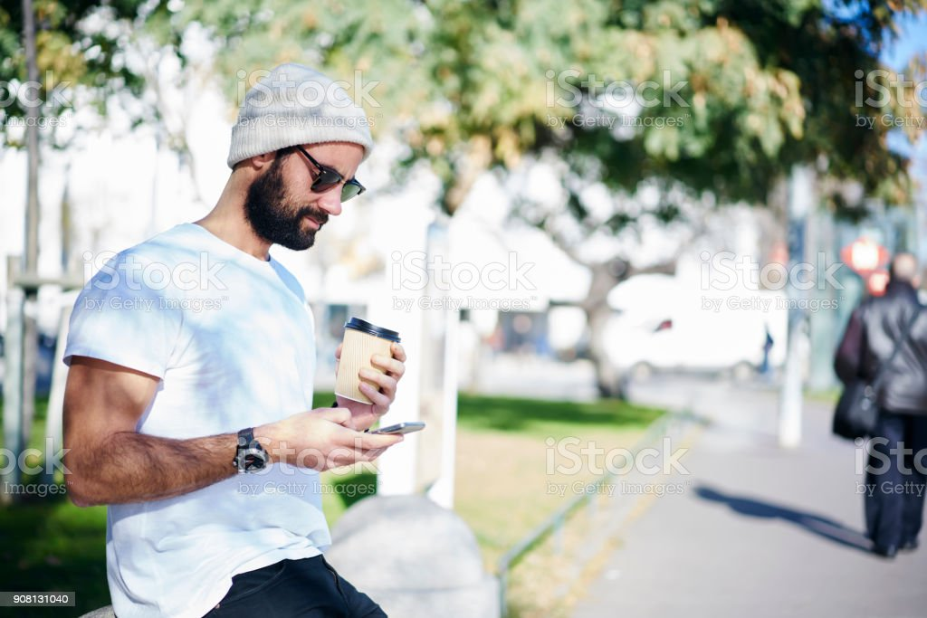 Handsome male hipster in trendy sunglasses resting watching video on smartphone connected to 4G internet outdoors, bearded hispanic model blogging on web site enjoying coffee to go and spring weather - foto stock
