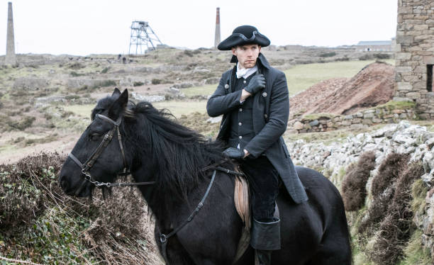 Handsome Male Horse Rider Regency 18th Century Poldark Costume with tin mine ruins and Cornish countryside in background stock photo
