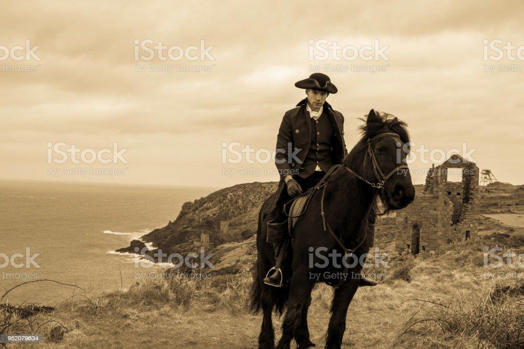 Handsome Male Horse Rider Regency 18th Century Poldark Costume with tin mine ruins and Cornish coastline in background stock photo