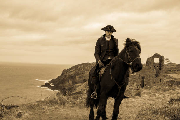 Handsome Male Horse Rider Regency 18th Century Poldark Costume with tin mine ruins and Cornish coastline in background stock photo