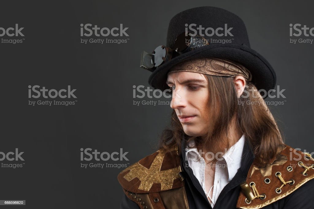 Handsome male in a hat-cylinder, Steam punk style. Retro man portrait over grey background. stock photo