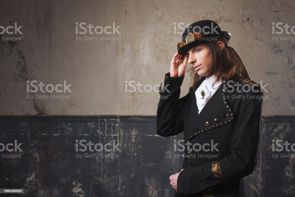 Handsome male in a hat-cylinder, Steam punk style. Retro man portrait over grunge background. stock photo