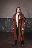 istock Handsome male in brown cloak, Steam punk style. Retro man portrait over grunge background. 688597064