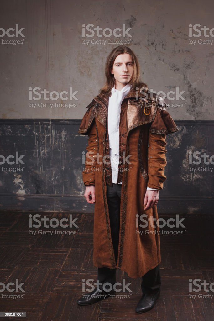 Handsome male in brown cloak, Steam punk style. Retro man portrait over grunge background. stock photo