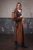 istock Handsome male in brown cloak, Steam punk style. Retro man portrait over grunge background. 688597086