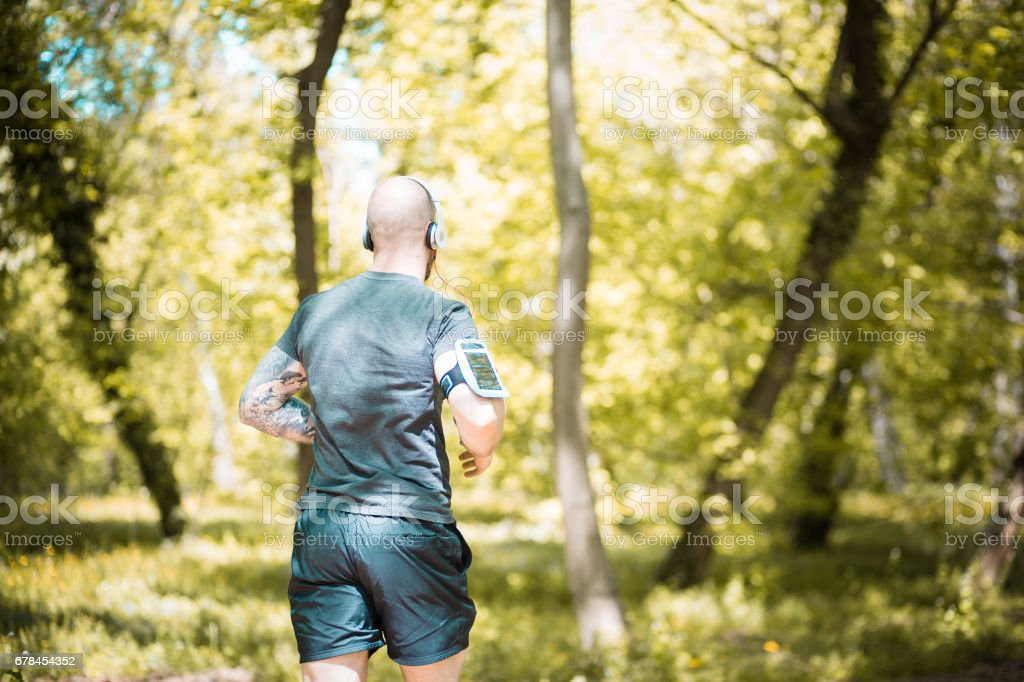 Handsome male, jogging in the park, wearing headphones, listening music royalty-free stock photo