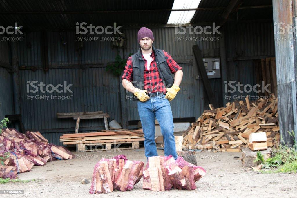 Handsome male lumberjack chops firewood in yard stock photo