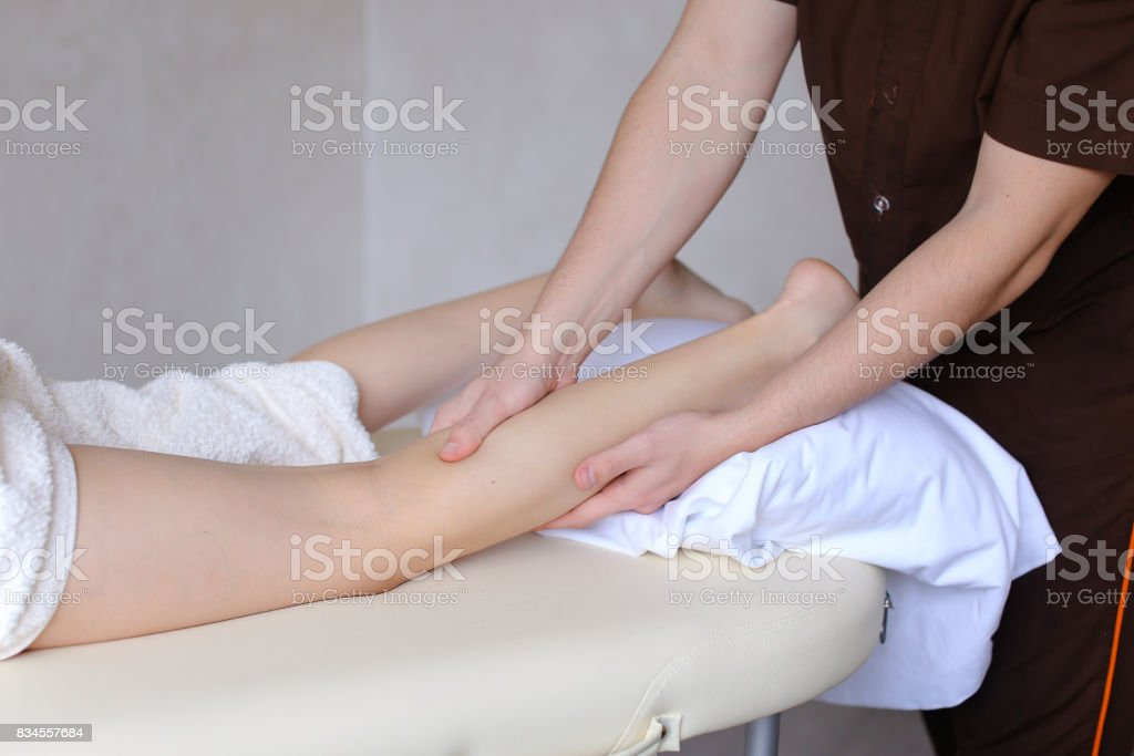 Clever guy massage therapist gently massages feet and rubs palms for...