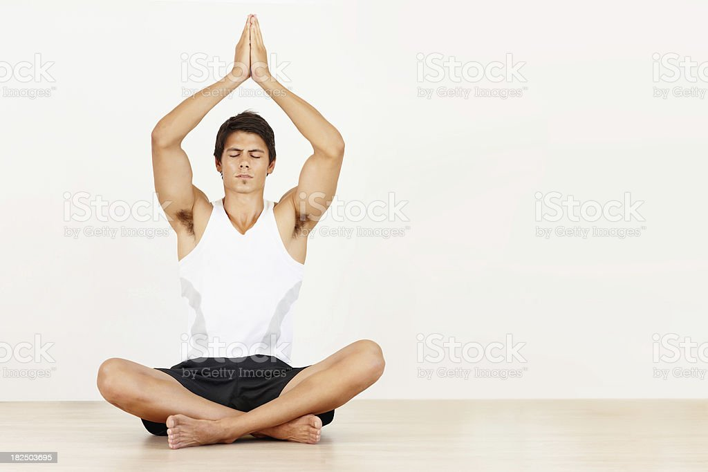 Handsome male meditating with hands joined above head royalty-free stock photo