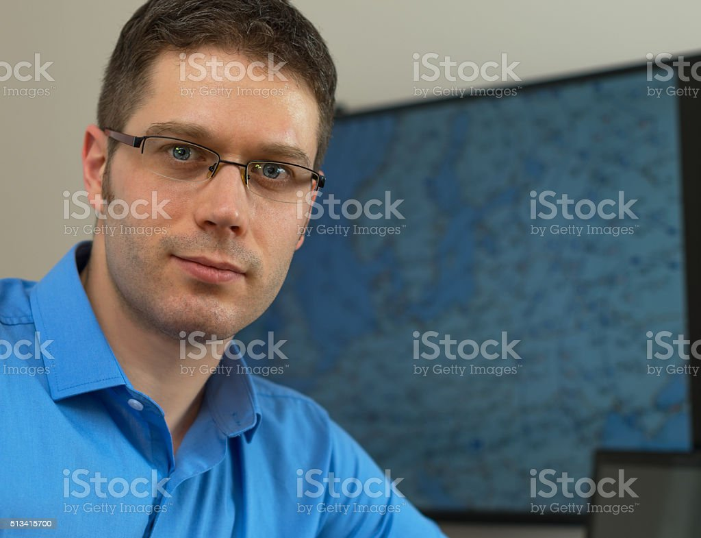 Handsome male meteorologist in glasses on his workplace. stock photo