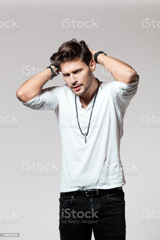 Handsome male model posing casuals Portrait of handsome male model in casuals with hands in hair looking at camera on grey background 25-29 Years Stock Photo