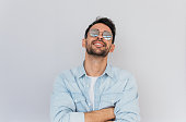 Handsome male model wearing trendy round mirror sunglasses and blue shirt having pleasant smile and white teeth posing against white background enjoy summer weather.People, lifestyle, emotions concept