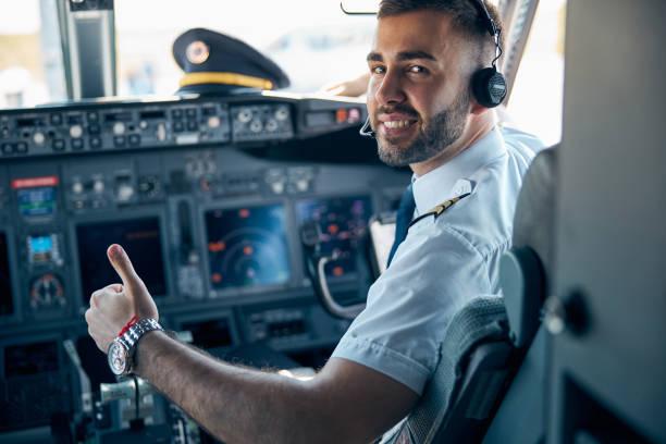 旅客機のキャビンでカメラでポーズをとるハンサムな男性 - パイロット ストックフォトと画像