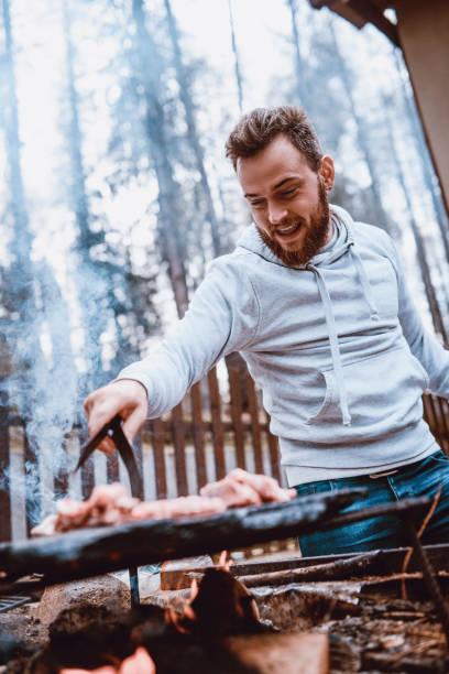 Hombre guapo preparar barbacoa en Picnic Familiar - foto de stock
