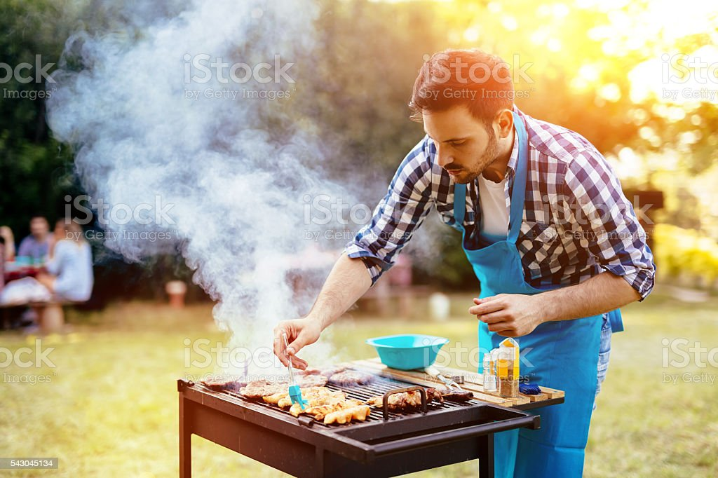 Handsome male preparing barbecue stock photo