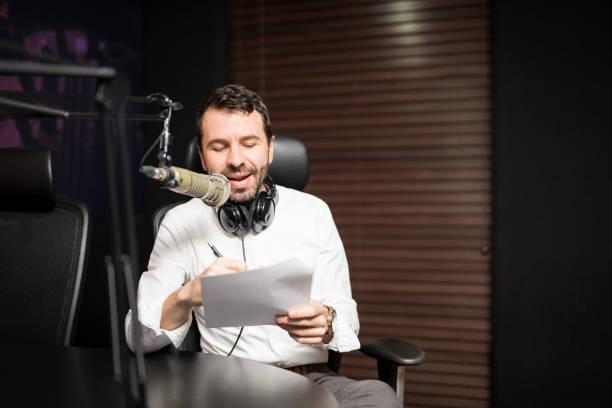 handsome male radio host in studio - talk in a radio foto e immagini stock
