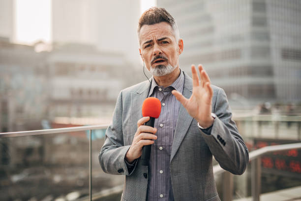 Handsome male reporter in live broadcasting relays today's news stock photo