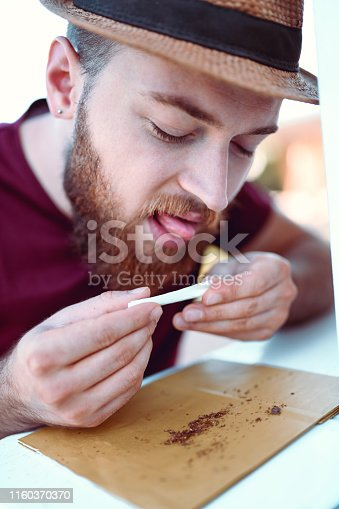 Handsome Male Rolling His First Cigarette