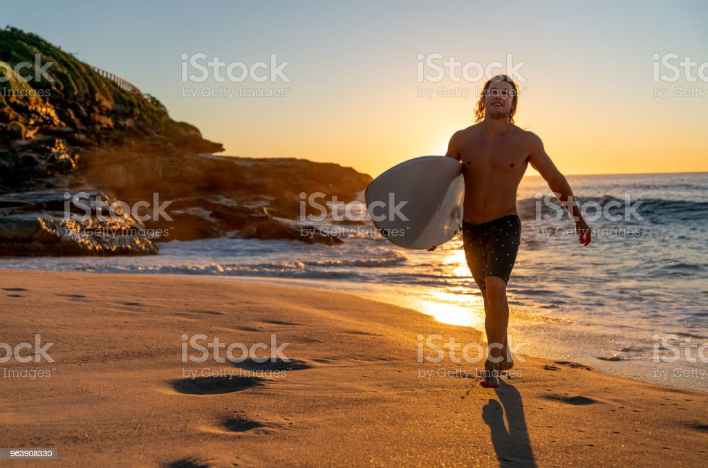 Handsome male surfer running at the beach and looking happy - Royalty-free Adult Stock Photo