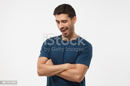 1045886560 istock photo Handsome male with crossed arms smiling and winking, looking at camera isolated on gray background 997461894