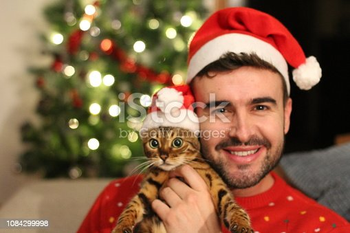 Handsome male with his cat during christmas.