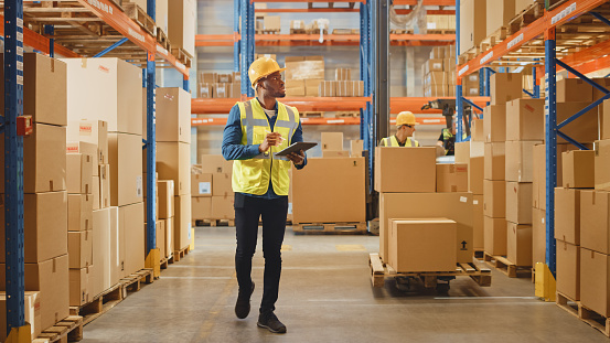 Handsome Male Worker Wearing Hard Hat Holding Digital Tablet Computer Walking Through Retail Warehouse full of Shelves with Goods. Working in Logistics and Distribution Center.