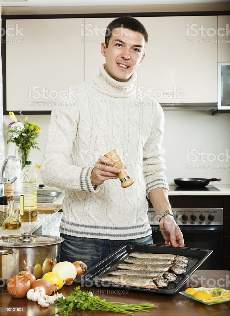 Handsome man adding spices in raw fish stock photo