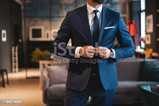 973213156 istock photo Handsome man adjusting his jacket while standing in modern office. 1194274023