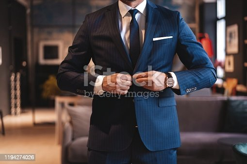 973213156 istock photo Handsome man adjusting his jacket while standing in modern office. 1194274026