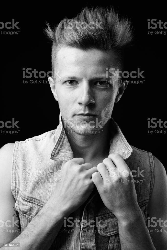 Studio shot of handsome man against black background in black and...