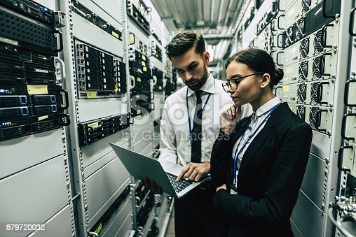 917307226istockphoto Handsome man and attractive woman are working in data centre. 879720032