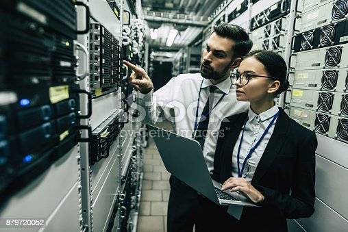 917307226istockphoto Handsome man and attractive woman are working in data centre. 879720052