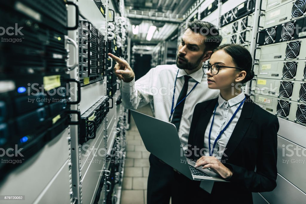 Handsome man and attractive woman are working in data centre. stock photo