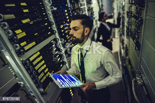 917307226istockphoto Handsome man and attractive woman are working in data centre 879720192