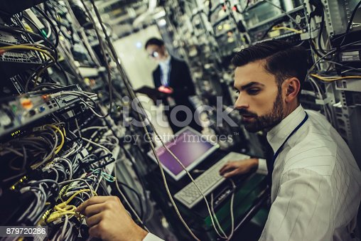 917307226istockphoto Handsome man and attractive woman are working in data centre 879720286