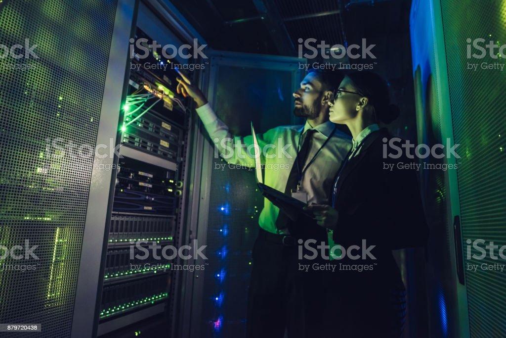 Homem bonito e atraente mulher estão trabalhando no centro de dados - foto de acervo