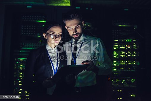 917307226istockphoto Handsome man and attractive woman are working in data centre 879720440