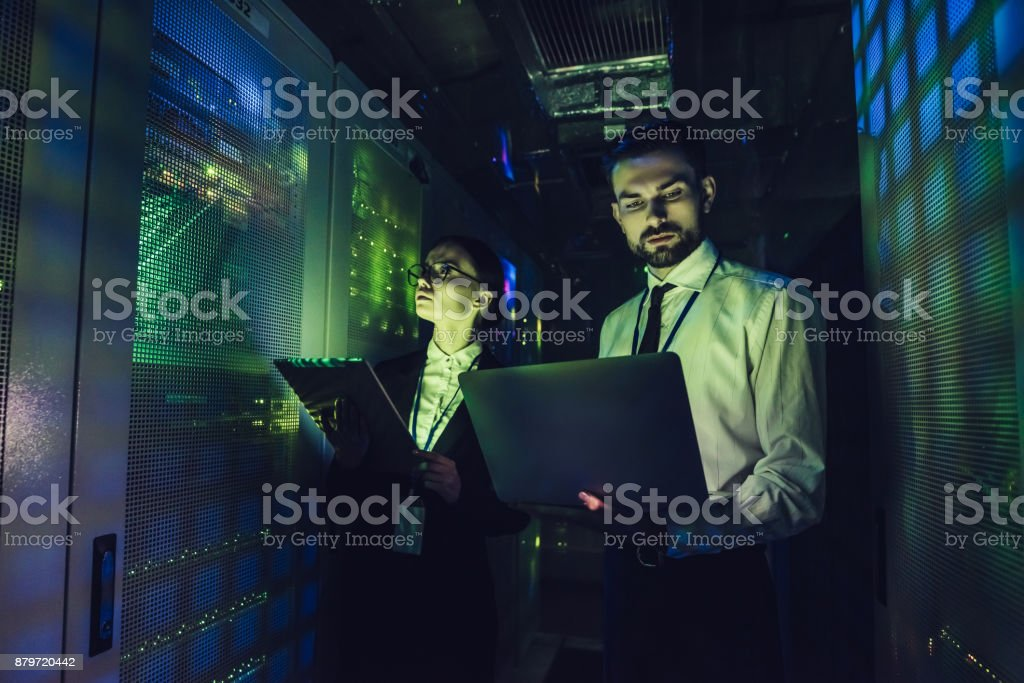 Handsome man and attractive woman are working in data centre stock photo
