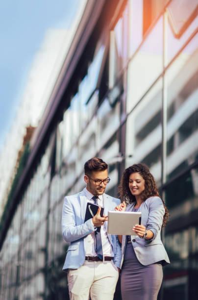 Hombre guapo y mujer hermosa como socios de negocios utilizando tableta digital al aire libre - foto de stock