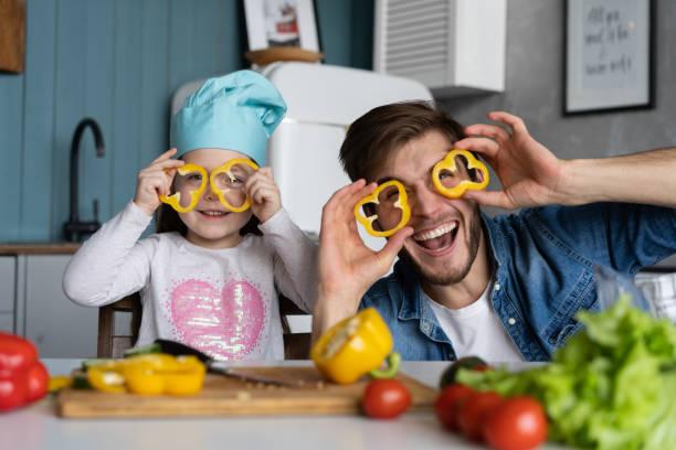 Der hübsche Mann und seine kleine süße Tochter kochen in der Küche. Salat machen. Gesundes Lifestyle-Konzept. – Foto