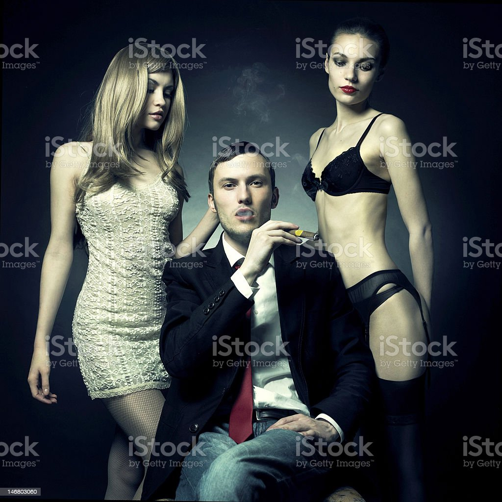 Handsome man and two women stock photo