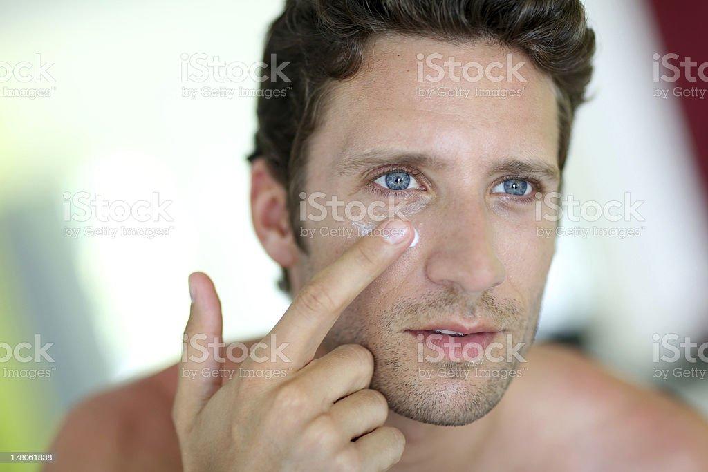 Handsome man applying cream stock photo