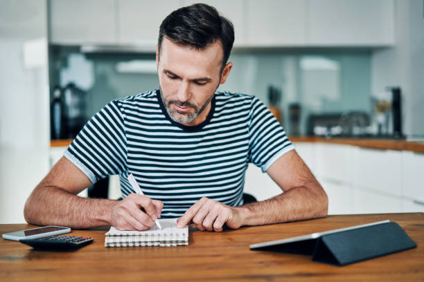 Handsome man at home and calculating home finance stock photo
