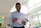 Handsome man at home going over his mail smiling very happy - Low angle view